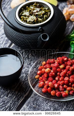 Black iron asian tea set with ripe strawberry on wooden background