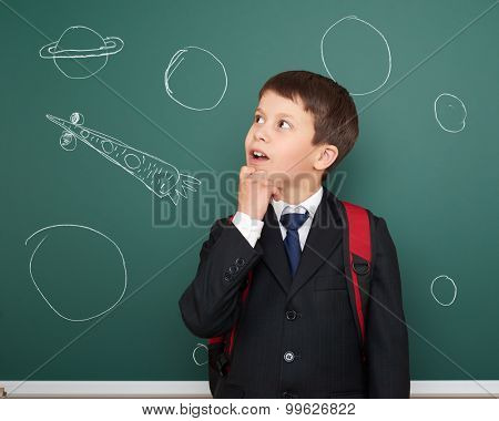school boy with drawing space rocket on board