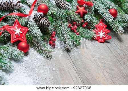 Fir tree branches with christmas decoration on old wooden board