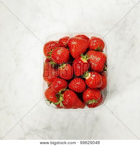 Transparent plastic tray with freshly picked strawberries