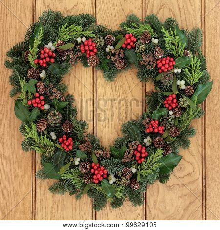 Christmas and winter heart shaped wreath with holly, mistletoe and greenery over oak background.