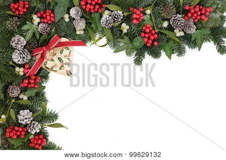 Christmas abstract background border with retro heart bauble decoration, holly, ivy, mistletoe, pine cones and blue spruce fir over white.