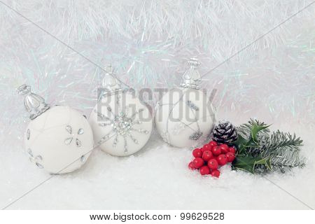 Christmas white bauble decorations with holly and fir on snow with decorative tinsel  background.