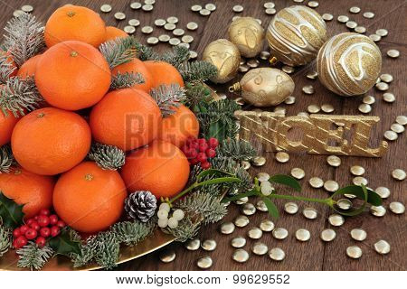 Christmas satsuma tangerine orange fruit, gold noel sign and bauble decorations, holly, mistletoe and spruce pine fir with snow over oak background.