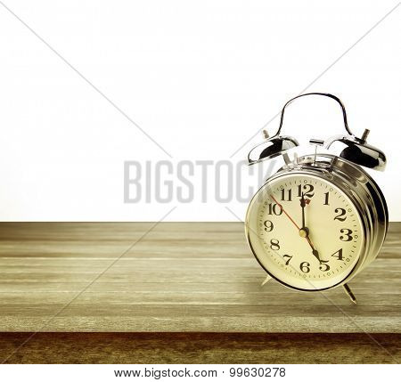 Alarm clock on table in front of plain background