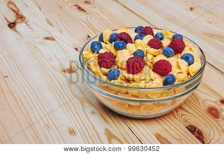 Corn flakes with fresh berries in bowl, on wooden background