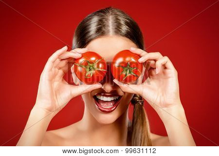 Beautiful laughing woman holding two ripe tomatoes before her eyes. Red background. Healthy eating concept. Diet.