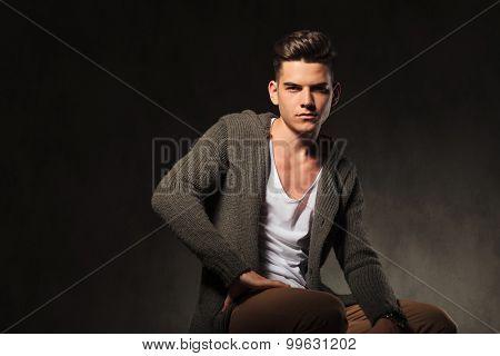 Portrait of a handsome casual man sitting on dark studio background.