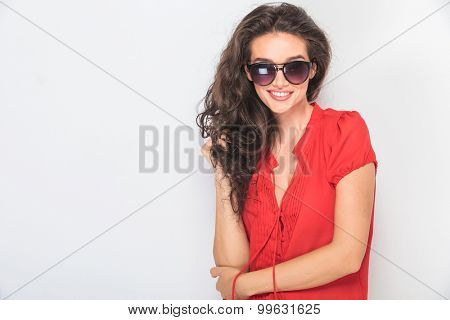 Smiling young woman holding her hand in the elbow while looking at the camera.