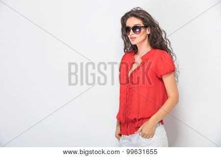 Beautiful young woman looking away from the camera while holding her hands in pockets.