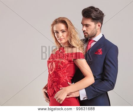 Sexy elegant woman looking at the camera while her lover is looking at her.