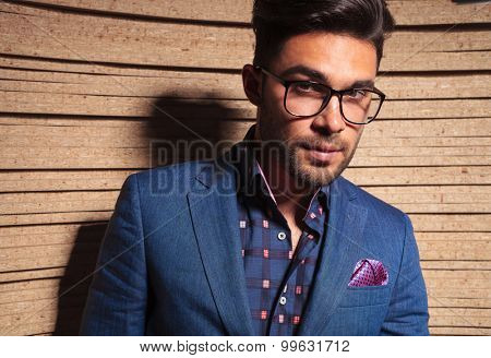 Close up picture of a handsome fashion man looking at the camera, on wood background.