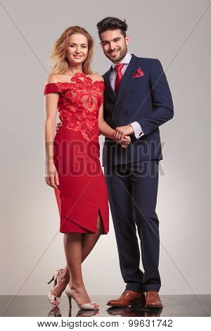 Happy elegant couple holding hands while standing on studio background.