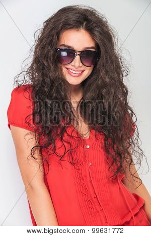Portrait of a young woman with curly hair wearing sunglasses.