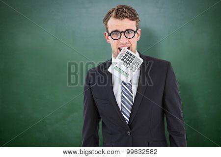 Geeky businessman biting calculator against green chalkboard