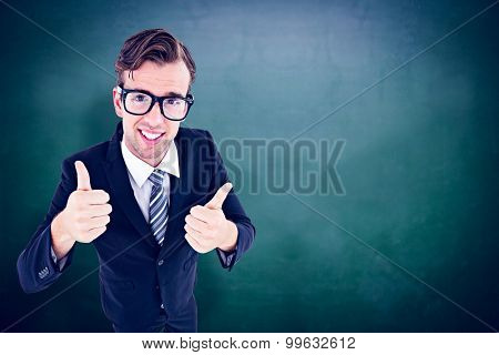 Geeky hipster smiling at camera with thumbs up against green chalkboard