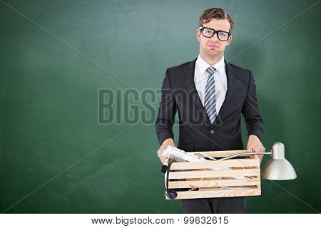 Sad geeky businessman holding box of his things against green chalkboard