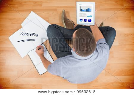 The word controlling and business interface against young creative businessman looking at tablet