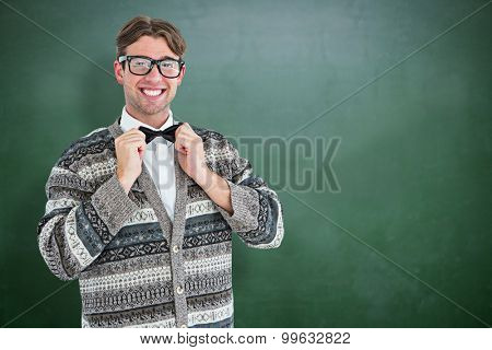 Happy geeky hipster with wool jacket against green chalkboard