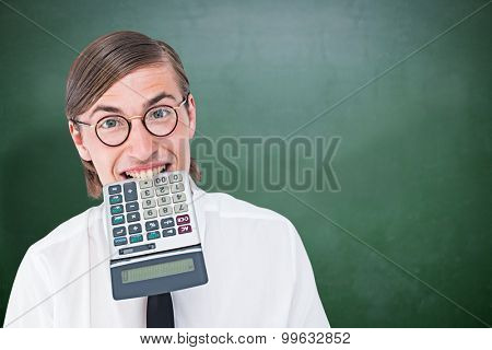 Geeky smiling businessman biting calculator against green chalkboard