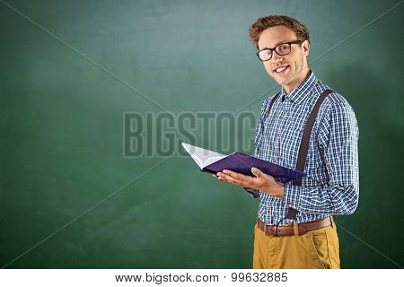 Geeky student reading a book against green chalkboard