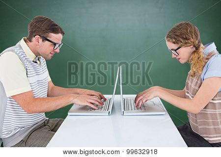 Geeky hipster couple using laptop against green chalkboard