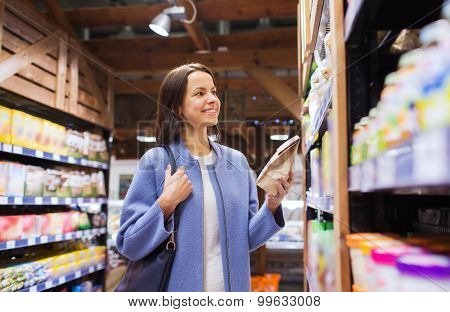 sale, shopping, consumerism and people concept - happy young woman choosing and buying food in market
