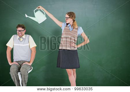 Geeky hipster holding watering can above her boyfriend against green chalkboard