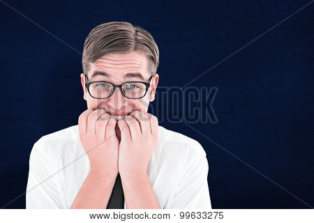 Geeky businessman looking nervously at camera against navy blue
