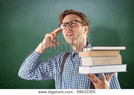 Geeky student holding a pile of books against green chalkboard