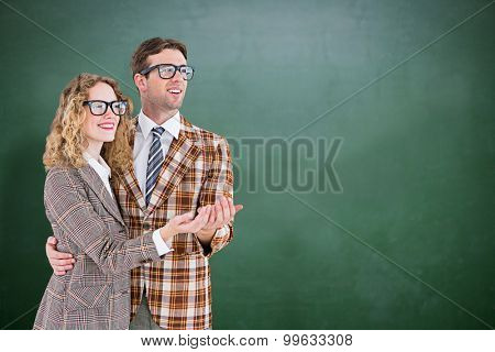 Geeky young hipster smiling at camera against green chalkboard