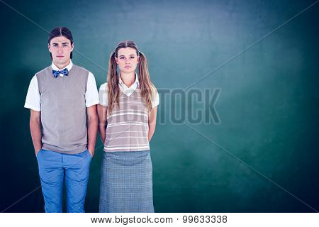 Unsmiling geeky hipsters looking at camera against green chalkboard