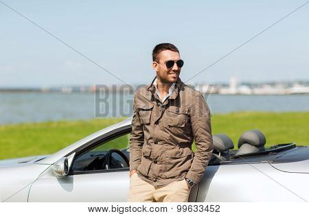 auto business, transport, leisure and people concept - happy man near cabriolet car outdoors