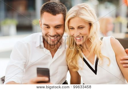 love, date, technology, people and relations concept - smiling happy couple with smatphone at city street cafe
