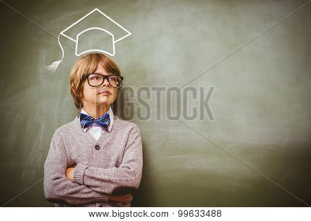 Graduation hat vector against boy with arms crossed looking up at blackboard