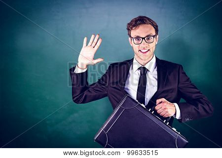 Young geeky businessman holding briefcase against green chalkboard