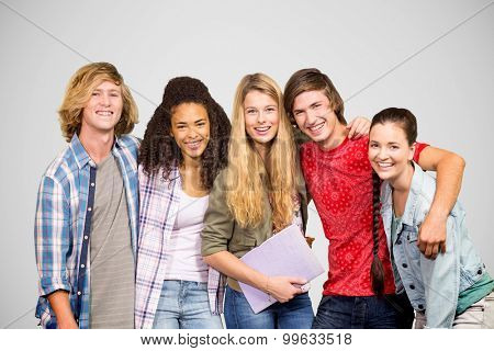 Cheerful college students in library against grey vignette