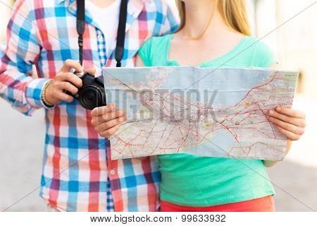 travel, tourism, technology and people concept - close up of couple with map and digital camera in city