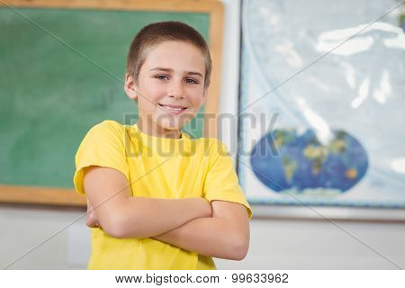 Portrait of smiling pupil with arms crossed in a classroom in school