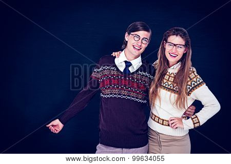 Happy geeky hipster couple embracing against blackboard