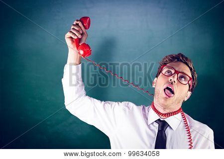 Geeky businessman strangling himself with telephone against green chalkboard