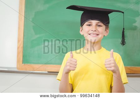 Portrait of smiling pupil with mortar board doing thumbs up in a classroom
