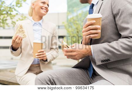 business, partnership, hot drinks and people concept - close up of smiling businessmen with coffee cups and sandwiches having lunch and talking outdoors