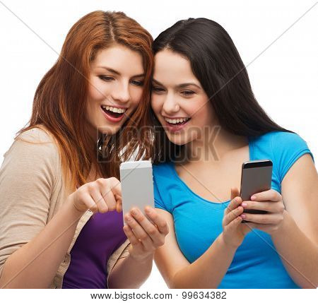 technology, friendship and people concept - two smiling teenagers pointing finger at smartphone screen