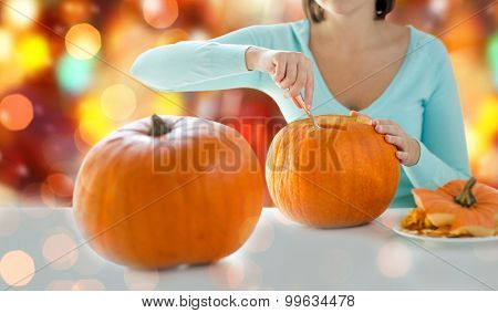 holidays, halloween, decoration and people concept - close up of woman carving pumpkins
