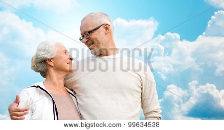 family, age, love, relations and people concept - happy senior couple over blue sky and clouds background