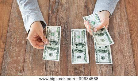 business, finance, saving, banking and people concept - close up of woman hands counting us dollar money on wooden table