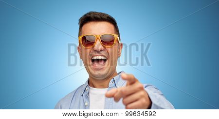 summer, style, emotions and people concept - face of laughing middle aged latin man in shirt and sunglasses over blue background
