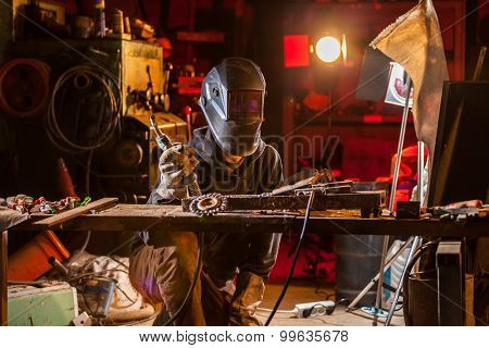 Welder working in workshop, many tools on table