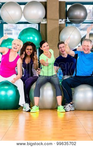 Men and women sitting on fitness balls in gym, diversity group of old, young, black and white people